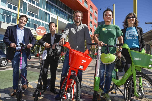 Representatives of Lyft, Lime, Bird and jump pose with their electric vehicles