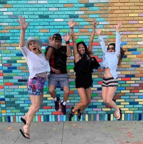 Artist Joe Nicoletti jumps with friends in front of Saskia mural